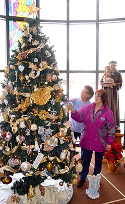 Kathleen Correia (rear) and Anna Mattia admire the ornaments of one of the Christmas trees in Holy Cross Mausoleum.