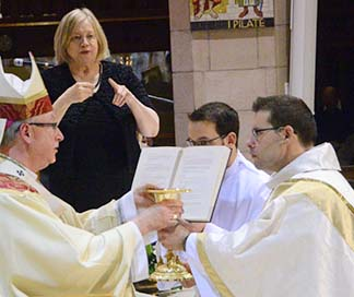 Archbishop Richard Smith presents Fr. Matthew Hysell with the sacred vessels used in celebrating the Eucharist.