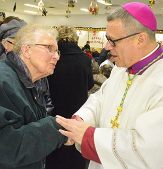 Bishop Paul Terrio converses with Jeannette Ozga, one of the faithful in the town of St. Paul.