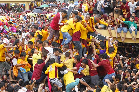 Pilgrims climb to touch the Black Nazarene during a procession in Manila, Philippines, Jan. 7. The wooden statue, carved in Mexico and brought to Manila in the early 17th century, is cherished by Catholics, who believe that touching it can lead to a miracle.