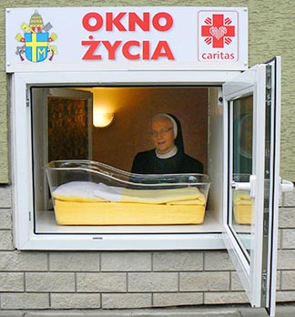 A nun is seen in the window of a baby hatch (called angel cradles in North America) inside the Sisters of Our Lady of Loreto residence in Warsaw, Poland.