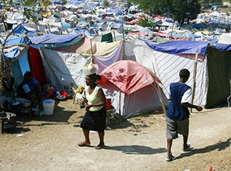 A woman and young man walk among tents at the makeshift camp on the Petionville Club golf course still needed after the 2010 earthquake in Port-au-Prince, Haiti.