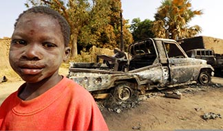 A boy stands near destroyed vehicles Jan 24 in Diabaly, Mali, which was recently liberated by French and Malian forces from Islamic rebels.
