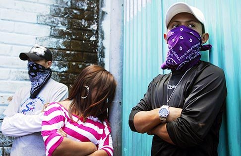 Masked members of El Salvador's Mara Salvatrucha (MS-13) gang participate in a pledge to reduce violence near San Salvador Jan. 24. Sponsored by the country's Catholic Church, the event involves gang members who promise not to commit violent acts in their communities.