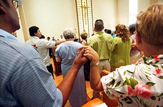 Cursillo members hold hands during Mass at a Cursillo retreat in the U.S. In the Edmonton Archdiocese, Cursillo holds separate weekend retreats for men and women.