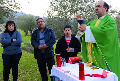 Father Ibrahim Shomali celebrates an outdoor Mass in an olive grove outside the Salesian Monastery in Beit Jalla, West Bank, Jan. 18. A planned routing of the Israeli separation barrier could isolate the monastery from the people it serves.