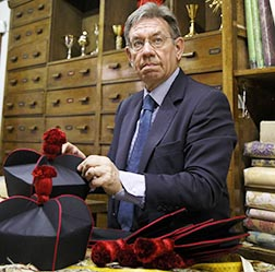 An employee at the Gammarelli clerical tailor shop in Rome shows clerical wear to a customer.