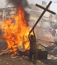 A demonstrator burns a cross during a protest in Lahore, Pakistan, March 9.