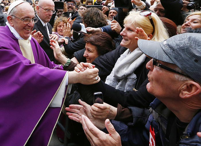 Pope Francis greets people after celebrating Mass at St. Anne's Parish within the Vatican March 17. The new pope greeted every person leaving the small church and then walked over to meet people waiting around St. Anne's Gate.
