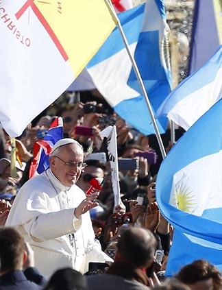 Flags are held up by pilgrims as Pope Francis makes his way through the crowd before his inaugural Mass at the Vatican March 19.