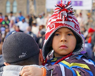 A young face peers over his father's shoulder as Northern Quebec Cree Whapmagoostul First Nation youth arrive.