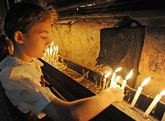 A girl lights a candle during the Catholic Vigil Mass in the Church of the Holy Sepulchre in the Old City of Jerusalem last year.