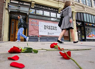 Flowers lie on the sidewalk at the site of the first Boston Marathon explosion as people walk along Boylston Street April 24.