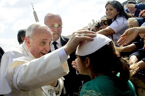 Pope Francis exchanges skull caps with a young girl after arriving for his weekly audience in St. Peter's Square at the Vatican May 8.