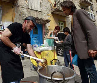Constantinos Polychronopoulos, an unemployed marketing specialist, distributes food portions at a soup kitchen for the poor in Athens, Greece.