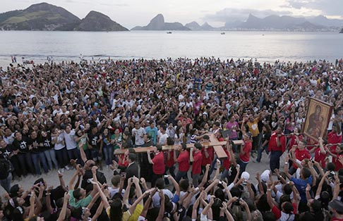 Young people carry the World Youth Day cross during its arrival in Icarai beach in Niteroi, Brazil, May 19. Pope Francis will travel to Brazil to attend the World Youth Day gathering July 23-28.