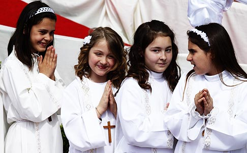First communicants wait in line as Pope Francis celebrates Mass at Sts. Elizabeth and Zechariah Parish on the outskirts of Rome May 26. The pope gave first Communion to 16 children.
