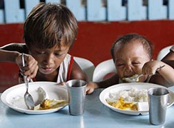 A boy and his younger brother eat their free meals May 22 during a feeding program at a slum area in Manila, Philippines.