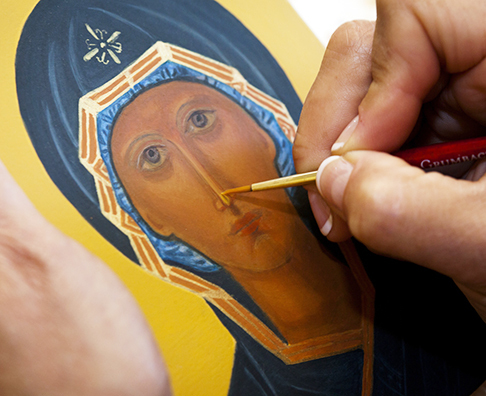 Teresa Foley paints detail on her icon of the Mother of God of the Sign May 25 at the home of iconographer Veronica Royal in Annandale, Va.