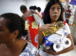 A woman carries products at a state-run supermarket in Caracas, Venezuela, June 4. Sporadic shortages of basic goods in the country can turn a roll of toilet paper into a rare commodity. Clergy and religious are worried about running low on altar wine and wheat to make hosts.
