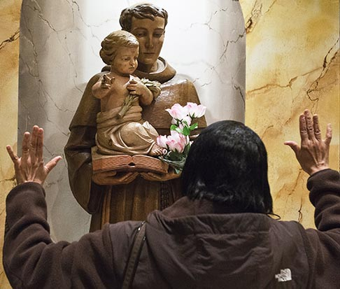 A worshipper prays before a statue of St. Anthony of Padua on his feast day, June 13, at St. Anthony Shrine in Paterson, N.J. St. Anthony of Padua was a Franciscan friar who was known for his gifted preaching and who died in Italy in 1231.