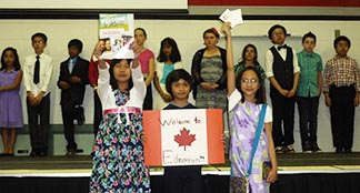 Julianne Suay, Mhel Mayor and Gabrielle Tian (front row, left to right) lead a presentation to a gym full of family and guests at St. Clement School May 29 about their care packages for newly-arrived immigrant families.