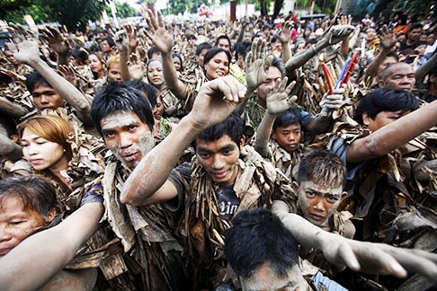 People covered with mud and dried banana leaves raise their hands for a blessing as they attend a Mass celebrating the feast of St. John the Baptist in the remote village of Bibiclat, Philippines, June 24. The origins of the festival and the reasons for the practice are unclear.