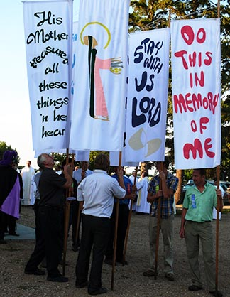 Men wait to carry banners in the procession at the start of Mass.