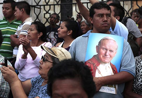 A man holds a poster with the image of Blessed John Paul II during an annual procession for the feast of the Assumption of Mary Aug. 15 on the streets of downtown Guatemala City.