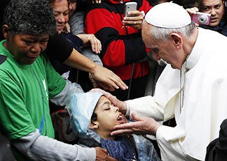 Pope Francis blesses a boy in the Varginha slum July 25, during his weeklong visit to Brazil.