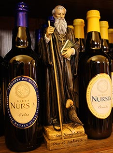 A statue of St. Benedict is seen between a bottle of