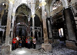 A Coptic Orthodox bishop prays with local residents at a damaged evangelical church in Minya, Egypt, Aug. 26. Egypt's military and interim government have blamed all the attacks on Christian properties on the Muslim Brotherhood, calling them the
