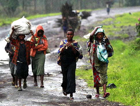 Civilians displaced by recent fighting between the Congolese army and M23 rebels carry their belongings as they walk along a road in Kibati village near Goma, Congo, Sept. 2. Bishop Willy Ngumbi Ngengele of Kindu said many communities in the area continue to suffer from the strikes committed by the M23 rebels.