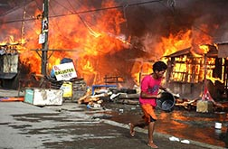 A man runs to fetch water to douse houses burning as the result of a firefight between government soldiers and Muslim rebels with the Moro Islamic Liberation Front in Zamboanga, southern Philippines Sept. 12.