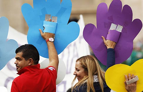 People wave coloured cutouts after Pope Francis celebrated a Mass with catechists in St. Peter's Square at the Vatican Sept. 29. The pope said being a catechist starts first with being with God, getting to know him and conforming one's life to the Gospel – a task that lasts a lifetime.