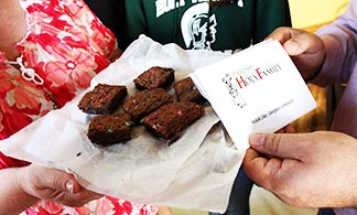 A woman holds a tray of brownies next to a sympathy card from members of a parish consolation ministry.