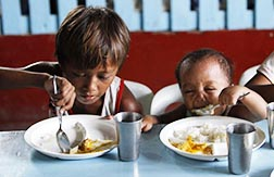 A boy and his younger brother eat their free meals during a feeding program at a slum area in Manila, Philippines.