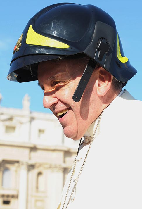 Pope Francis wears a firefighter's helmet as he arrives to lead his general audience in St. Peter's Square at the Vatican Oct. 16.