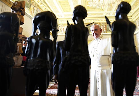 Pope Francis looks at ebony statues he received as a gift from Equatorial Guinea's President Teodoro Obiang Nguema Mbasogo during a meeting at the Vatican Oct. 25.