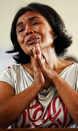 Rosario Capidos cries while thanking God that she and her family survived Typhoon Haiyan as she prays during Mass inside the damaged Minor Basilica of the Holy Child Nov. 17 in Tacloban, Philippines