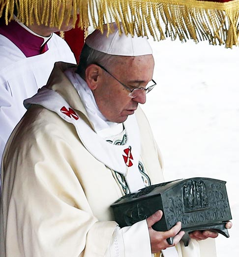 Pope Francis holds a bronze reliquary containing the relics of St. Peter the Apostle on the altar during a Mass in St. Peter's Square at the Vatican Nov. 24. The bone fragments, which were discovered during excavations of the necropolis under St. Peter's Basilica in the 1940s, are kept in the pope's private chapel but had never been displayed in public.