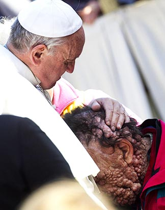 Pope Francis embraces Vinicio Riva, 53, during his general audience at the Vatican Nov. 6.