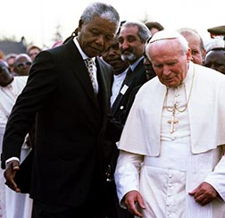 South African President Nelson Mandela assists Pope John Paul II at the Johannesburg International Airport in 1995.