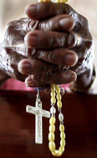 A worshiper holds a rosary inside the Basilica of the Holy Child in Tacloban, Philippines. For Filipinos, the final nine days leading to Christmas have special meaning.