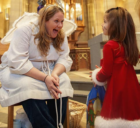 Katherine Russell, dressed as an angel, tells four-year-old Nori Bellucci-Mattice about the night Christ was born during a living Nativity Dec. 7 at Sacred Heart Cathedral in Rochester, N.Y.