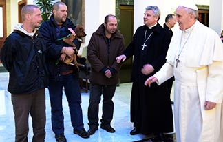 Pope Francis talks with three men Dec. 17 who live on the streets near the Vatican. For his 77th birthday, the pope celebrated morning Mass and had breakfast with the men.