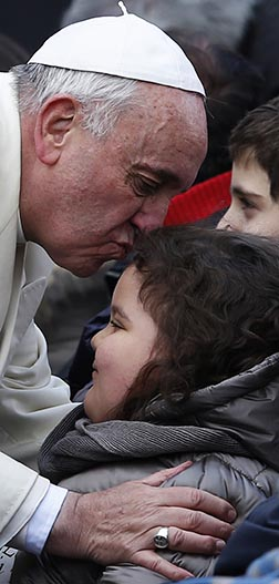 Pope Francis kisses a girl in a wheelchair during his general audience in St. Peter's Square.