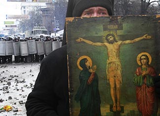 A clergyman holds a religious picture during a rally by pro-European Union protesters in Kyiv, Ukraine, Jan 21.