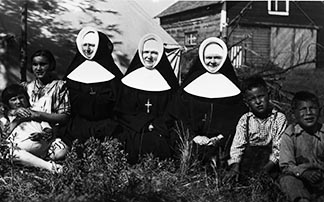Three Sisters of the Assumption are shown with students at Ermineskin Indian Residential School near Hobbema in this photo dated 1940.