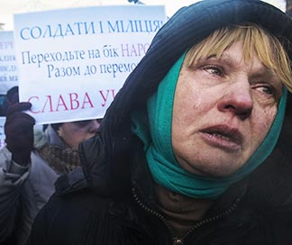 A woman cries as she and others appeal to Ukrainian police troops at the site of clashes with protesters in Kyiv Jan 24. Protests became violent in mid-January.